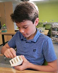 Tony Rossi works on his 3-D printer house, one of many projects students work on during Innovative Lab