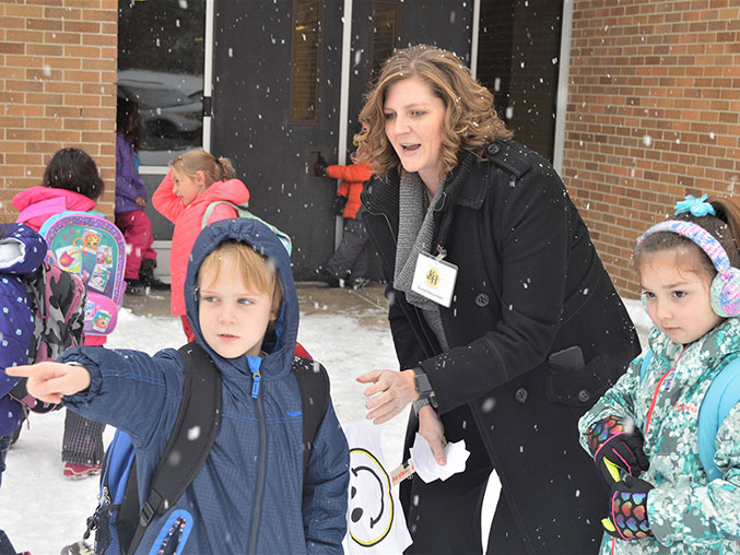 Parent volunteer Danielle Storey makes sure kindergartners Gabriel Hrycyk, pointing, and Audrina Coronado are picked up by their parents after school