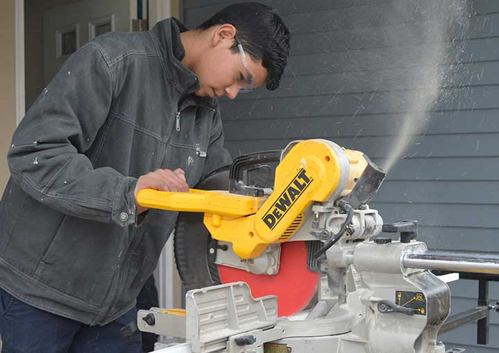 Junior Gonzalo Mora saws a piece of molding for a Habitat for Humanity house on Gold Avenue NW