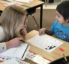 Literacy expert Patti Konarska helps a student with letters (Photo courtesy of Kyle Mayer)