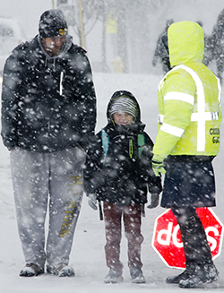 Patrick Scranton picks up his son, Jaxon, and chats with Kattie Eason, before she helps them cross a busy Wealthy Street SE in a snow storm