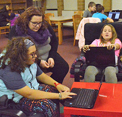 Sixth-graders Kyla Robinson (left) and Natalie Trader work on the computer app with help from robotics coach Meghan Bartoszek