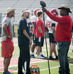Alanowski chats it up with coaches Dion Charity, left, and James Stokes