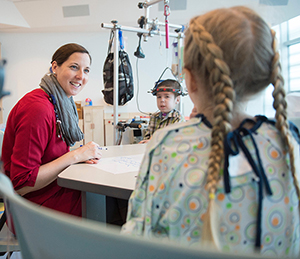 """Sarah Smith works with Dana (in pigtails) and Jacob on """"Niceness Ninjas"""" in Club TCB (photo courtesy Helen DeVos Children's Hospital)"""