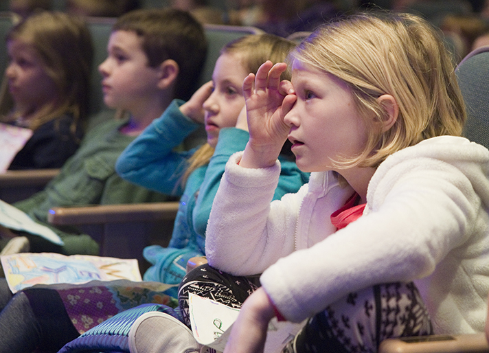 First-grader Violet Hoogenstyn and her classmates intently follow along