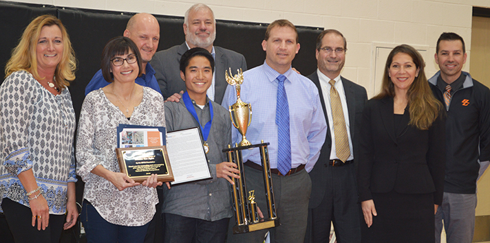 Byron Center High School senior Braden VanDyke receives his trophy, surrounded by Byron Center Public Schools representatives, his parents and members of the SIFMA Foundation