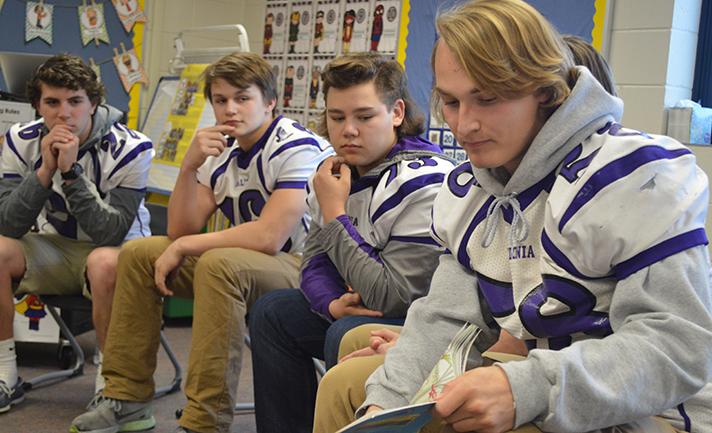 From left, football players Ty McClellan, Cam Watrous, Carter Osborn and Evan Vermetti visit kindergartners