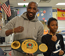 Professional boxer and entrepreneur Parnell Gates shows his belt to sixth-grader Quijuan Madion-Lewis