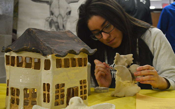 Senior Vanessa Flores works on and displays an array of clay pieces