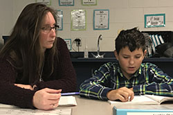 Paraprofessional Lisa Batchelor works on reading with sixth-grader Austin Stauffer