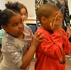Second-grader Josiah Sutton sails through the Lake of Trust, pushed by a classmate