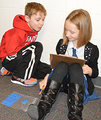 Third-graders Justine Meade and Julian Witt use trial-and-error to draw different shapes with the same area