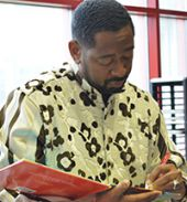 """Author and educator Byron Garrett signs his children's book, """"There's Greatness on the Inside,"""" following his presentation"""