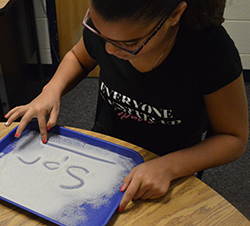 Southeast Kelloggsville Elementary School fourth-grader Aubrianna Vernon uses different methods to learn consonant blends, including writing in sand