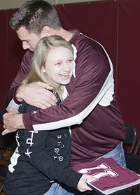 """Genny Swan, a """"Be an 11"""" winner, is hugged by a school mentor"""