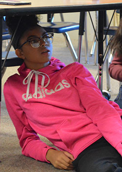 """Cydney Hansma, of Kelloggsville Middle School, finds a spot under the desk after being declared """"out"""" during a game in TEAM class"""