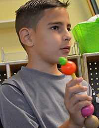 Fourth-grader David Espinoza, who is from Cuba, uses beads that correspond to questions to grow his vocabulary