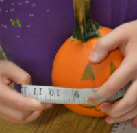 A student finds the circumference of a pumpkin