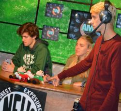 Anchors Brett Van Wagoner and Linnea Eastburg prepare to go live while Shane Sebuck checks their microphones