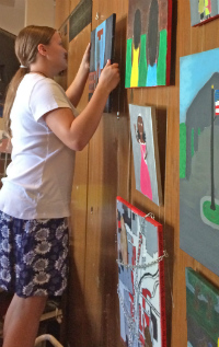 Middle-schooler Elinor Edlund hangs her painting in Fountain Street Church downtown (courtesy photo)