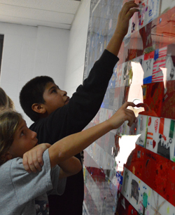Godfrey-Lee students find their tiles in the assemblage of pieces