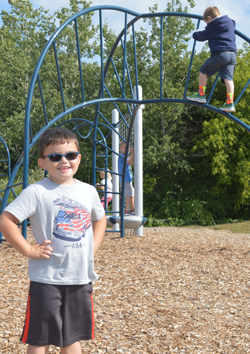 Kindergartner Owen Wing takes a break while playing on the new playground