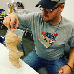 Andrew Schauver from Ingham ISD builds something out of wood planks