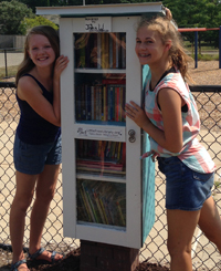 Lily Howland, left, and Chloe Grifhorst designed and built a Little Free Library to share their love of reading with the community