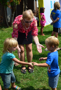 Assistant Superintendent JoAnn Spry dances to pop music with children during the Cedar Springs Mobile Estates back-to-school kickoff