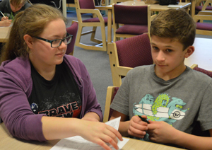 Junior Emily Sternburgh lends a hand to a Mill Creek Middle School student