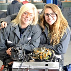 Sparta seniors and Automotive Technology students Alyssa Graham (right) and Tiffany Tasma lean on a diesel engine