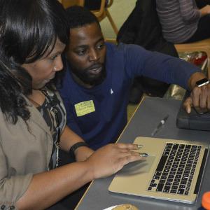 Stasha Gilbert gets tips on using her MacBook Air from Apple technician Segun Oyesile