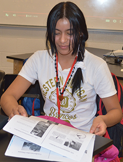 Kenia looks over materials in class at East Kentwood High School