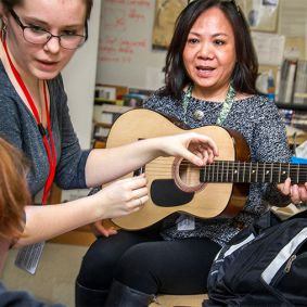 Le Tran models holding a guitar for Ben Ward's drawing with Mary Moyer advising on proper guitar technique