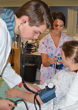 Senior Alex Hicks practices taking blood pressure