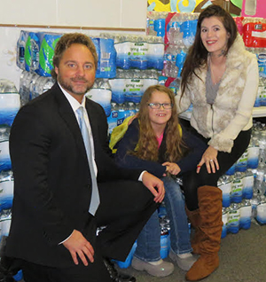 McFall Elementary Principal Jon Washburn, Scarlette Liesenfelder and Scarlette's mom, Macenzie Smallwood, were overwhelmed with the amount of water collected for people in Flint
