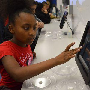 Ayzjah Jackson enters information at an iPad station