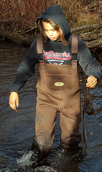 Cedar Springs High School freshman Ebonye Hunter searches Cedar Creek for leaf packs placed in mid-October for a biology experiment to research water quality