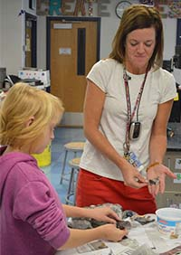 East Grand Rapids Middle School art teacher Holly Lampen works on paper mache frogs with seventh-grader Carrie Kirchgessner