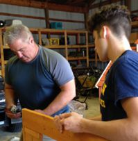 Student Josh Carter assembles a playhouse with Doug Gallup, Byron Center Public Schools Director of Transportation
