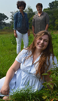 """Senior Pearl Chapman, foreground, with teachers Lynn Cvengros (left) and Dolores Keeley amid raspberry and blueberry rows on Forest Hills Eastern High land. The berries were planted through a grant from the Forest Hills Education Foundation as a """"seed"""" project of the edible schoolyard"""