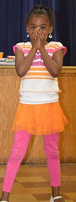 West Kelloggsville Elementary second-grader Omariyah Wilson-Smith reacts to magician Tom Plunkard's tricks