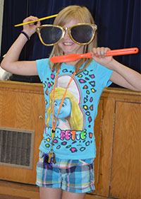 West Kelloggsville Elementary third-grader Thaila Spencer works on combing her hair and brushing her teeth at the same time during the magic show