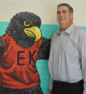 Principal John Keenoy stands next to Freddy the Falcon, which stands at the end of mural
