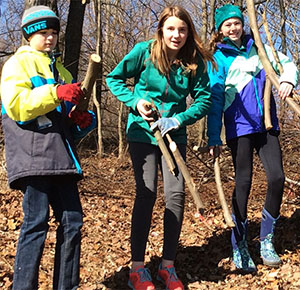 Students Ryan Alexander, Hailey Castor and Ava Mataj remove logs and branches after cutting autumn olive