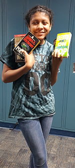 Eighth-grader Vanessa Brown holds books to donate