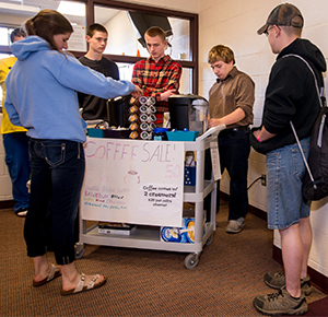 From left, Spencer Zuidema, Max Frozley and Tim Hudson service customers from behind the coffee cart during a morning hallway sales session