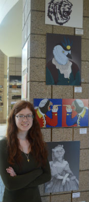 Marissa stands near her collection of art displayed in the high school's hallway