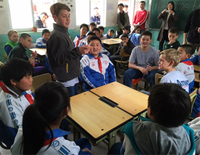 Sixth-grader Ethan Clark (standing) speaks to a class of students at the Fang Shan Chuangwei Primary School