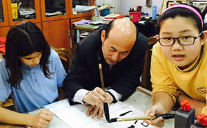 Averie Fitzjohn (in blue) receives instruction in calligraphy from a teacher at the Beijing No. 2 Experimental Primary School, Yihai Campus
